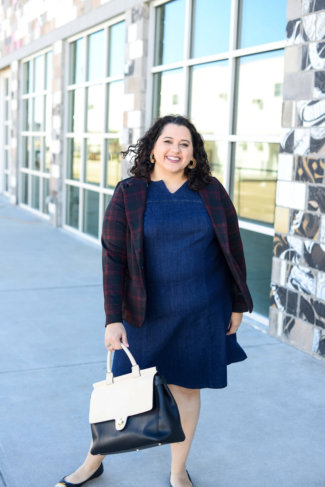 Wearing a denim dress to work is possible by pairing it with a great blazer
