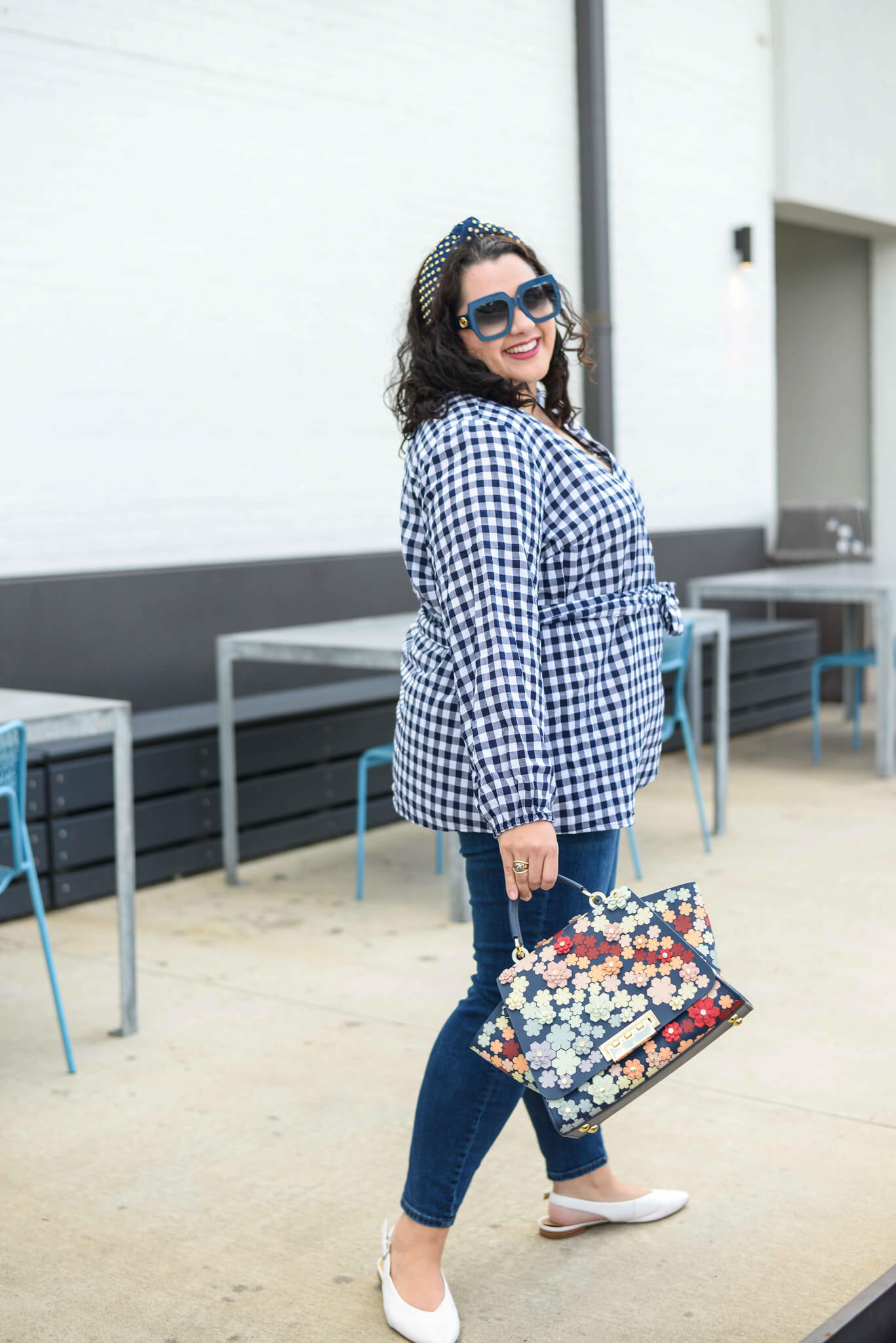 The perfect preppy fall transition outfit includes a navy and white plus size gingham top, skinny jeans and embellished headband